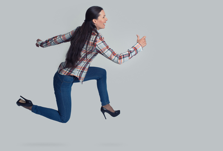 hasten: Full length portrait of woman running sideways. Isolated over gray Stock Photo