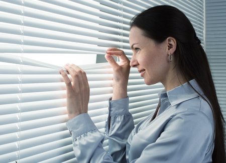 waiting glance: office worker looking through window blinds to the street