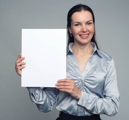 30 year old: Smiling 30 year old woman holding blank card. Isolated on grey background Stock Photo