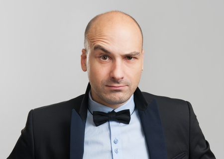 eyebrow raised: thoughtful bald business man with a raised eyebrow Stock Photo