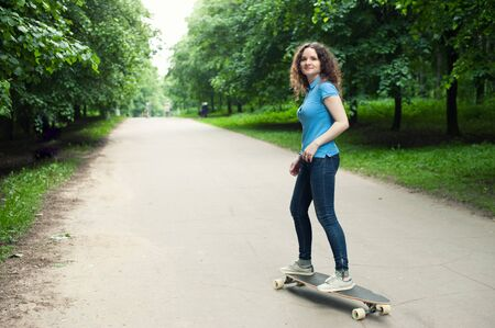 longboard: Beautiful young girl with longboard at the park
