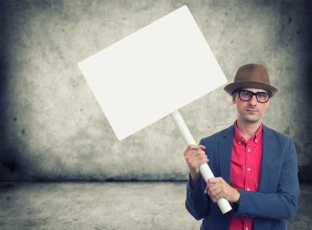 protest sign: trendy man holding blank protest sign with copy space
