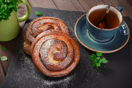 afters: Homemade cream roll and cup of tea on rustic background Stock Photo