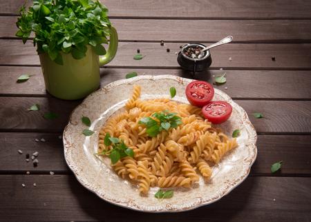fusilli: fusilli pasta on a plate. Rustic wooden table Stock Photo