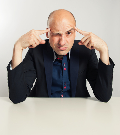 raised eyebrow: funny bald businessman trying to think seriously. Man Sitting at desk Stock Photo