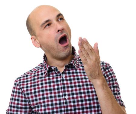sleepiness: Bald man yawning isolated on a white background