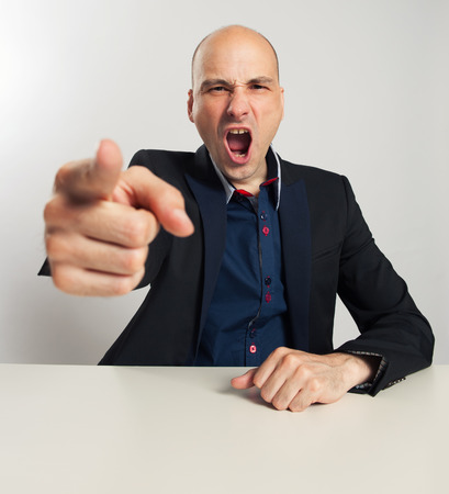 Angry businessman yells and pointing his finger at you. Man sitting at the desk