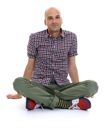 chinos: casual bald man sitting with legs crossed. isolated on white Stock Photo