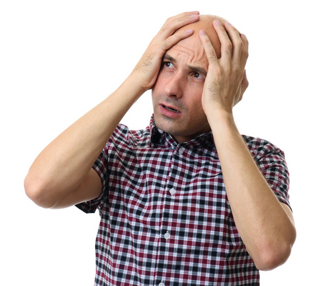 clutching: frightened man looking away clutching his head in his hands. Isolated