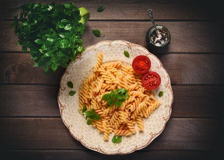 table top: pasta on a plate on rustic wooden table. Top view