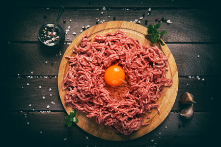 chopped red meat. forcemeat on a wooden background.