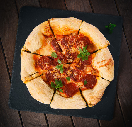 table top: pepperoni pizza on a wooden table. Top view Stock Photo