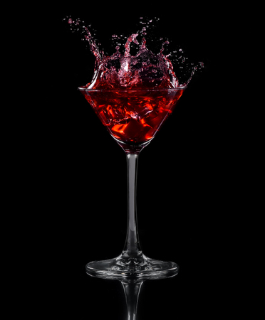 Ice cube dropped into a glass of grape juice. Black background
