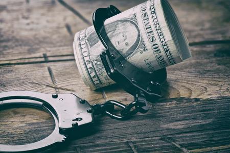 delito: Las esposas y el dinero sobre la mesa de madera. Dólares. concepto de delito fiscal