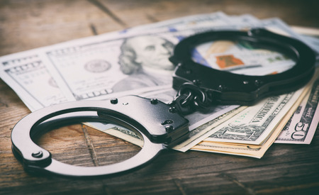 criminal: Handcuffs on money. US dollars. Criminal concept Stock Photo
