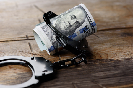 Money in handcuffs. Us dollar currency. Security concept