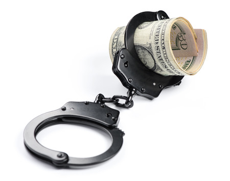 Money and handcuffs isolated on white background