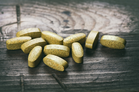 dietary supplements: Green tablets. dietary supplements on a wooden table