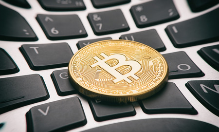 ltc: Golden bitcoin coin on a computer keyboard Stock Photo