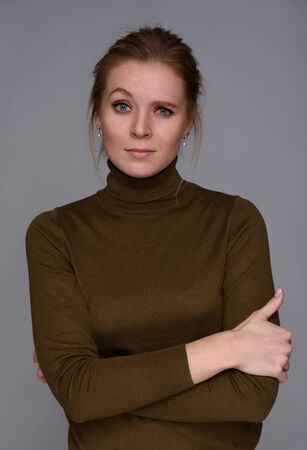 eyebrow raised: Beautiful confused woman with a raised eyebrow. Isolated on grey Stock Photo