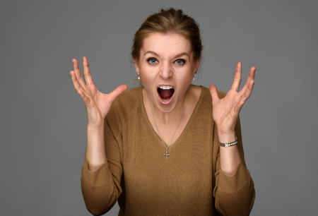 portrait of an angry woman over gray background Stock Photo