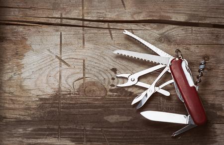 vieux couteau suisse sur un fond en bois. Vue de dessus avec espace copie
