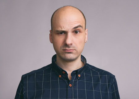 Confused guy. Puzzled young bald man. Isolated on gray background