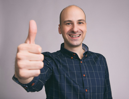 Happy handsome bald man showing thumbs up photo