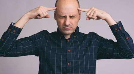 Bald man thinks intensely on gray background photo