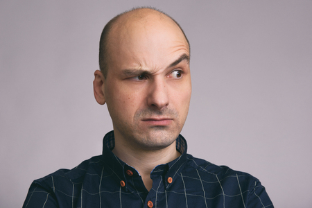 Serious bald man with raised eyebrow looking away photo