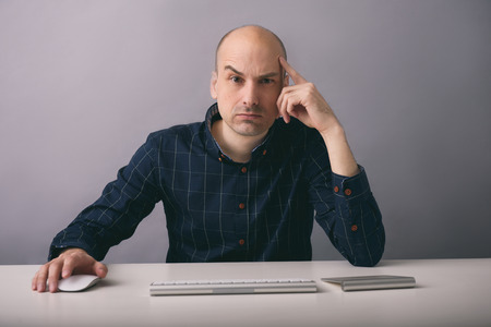 Guy works on computer. Serious man sitting at the desk and thinking photo