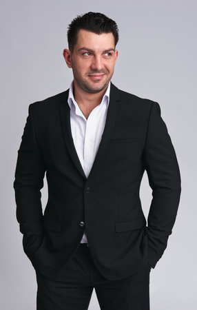 Handsome man in black suit smirking. Isolated on grey. Studio shot