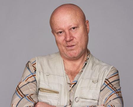 portrait of handsome skeptical senior man isolated on grey background
