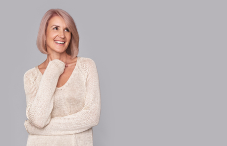 happy beautidul middle aged woman isolated on grey background Stock Photo