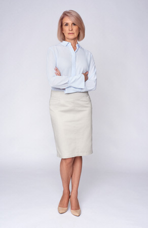 beautiful senior business woman. Full length portrait. Isolated on grey Standard-Bild