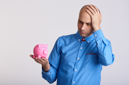 Worried businessman looking at piggy bank. Financial crisis and money saving concept.