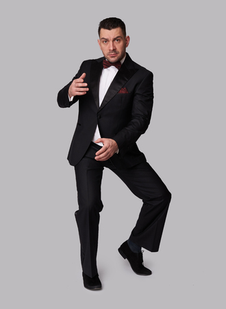 man in black suit. Full length portrait of a handsome guy in tuxedo. Studio isolated Archivio Fotografico