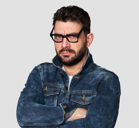 serious stylish young bearded man is wearing spectacles and denim clothes thinking 免版税图像