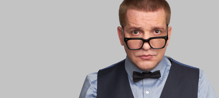 Handsome guy in glasses and bow tie isolated with copy space