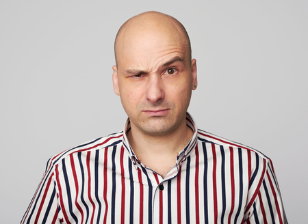 Serious angry man raised eyebrow. Bald guy looking at camera. Isolated on grey Archivio Fotografico