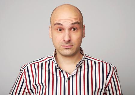 amazed bald man. Middle aged guy wearing shirt isolated over grey studio wall