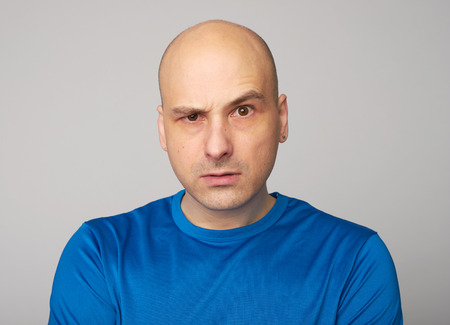 Serious bald man with raised eyebrow looking at camera. Displeased guy isolated over grey background