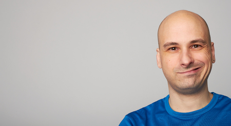 Bald man making a funny face. Smirking guy isolated on gray background