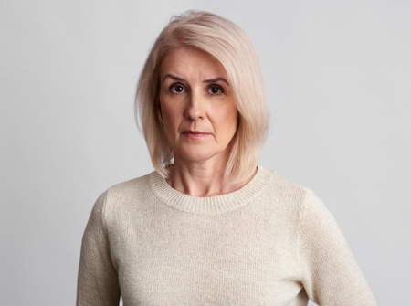 sad beautiful aged woman wearing sweater over grey studio wall. Standard-Bild