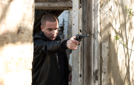 man is aiming with a pistol. Criminal