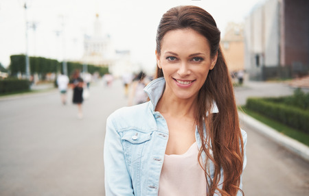 Portrait of happy woman standing in the street. Pretty smiling girl looking at you