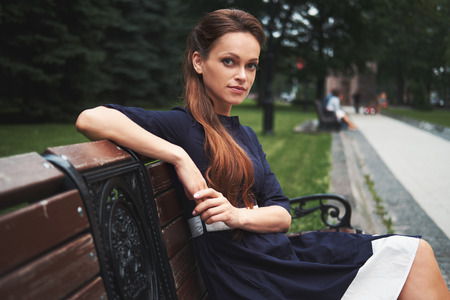 pretty woman sitting on a bench in the city park