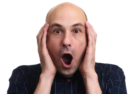 Headshot of shocked stressful bald man keeps hands on head, isolated over white blank wall. Wondered and amazed guy