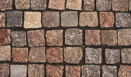 Old granite pavement background. Retro cobblestoned road texture