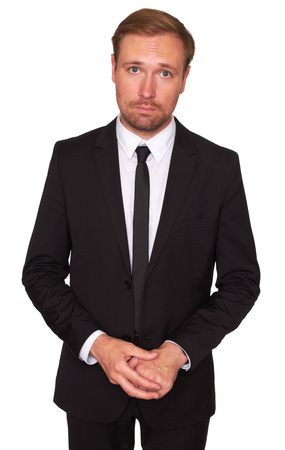 Young businessman standing over white background. Sad business man looking at camera. Isolated Stock Photo